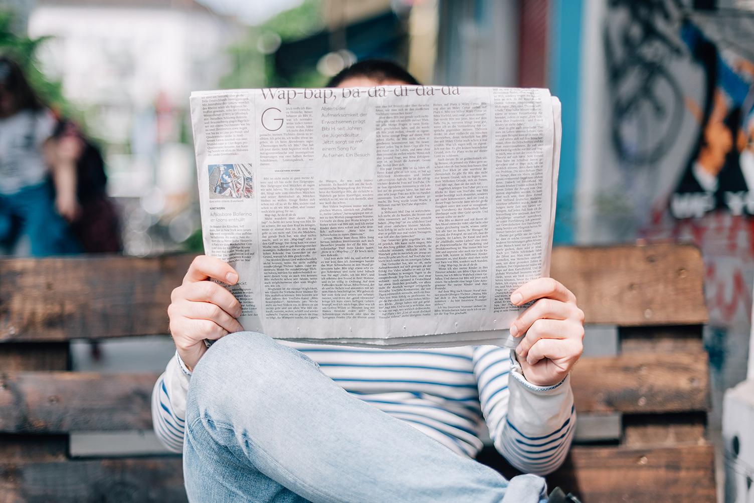 Sitzender Mann mit aufgeschlagner Zeitung